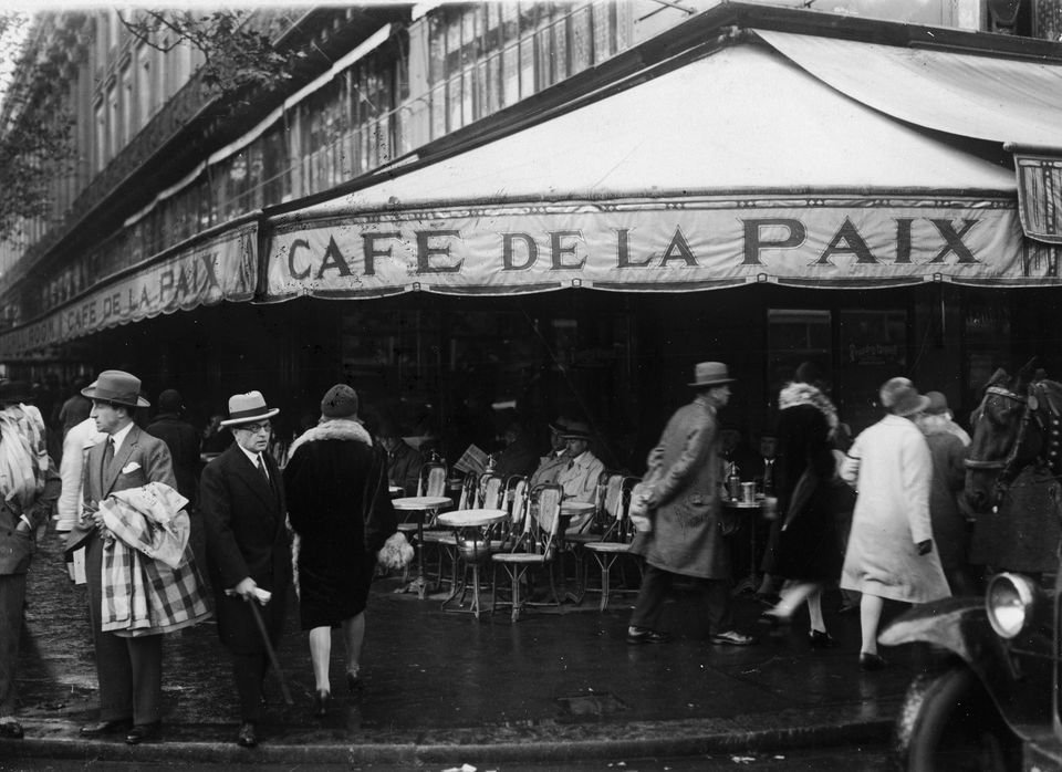 Pedestrians walk past on the sidewalk as patrons sit and relax at the Cafe de la Paix during a break in the rain, Paris, 1930s