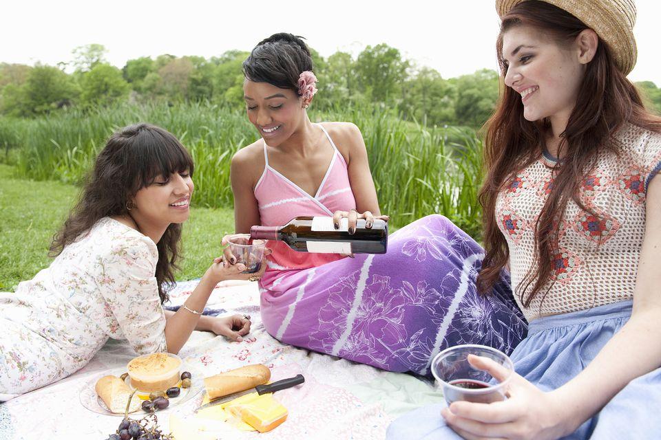 Women drinking wine in a park