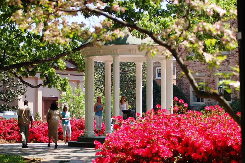 The gazebo known as The Old Well on UNC Chapel HIll campus surrounded by blooming flowers in spring