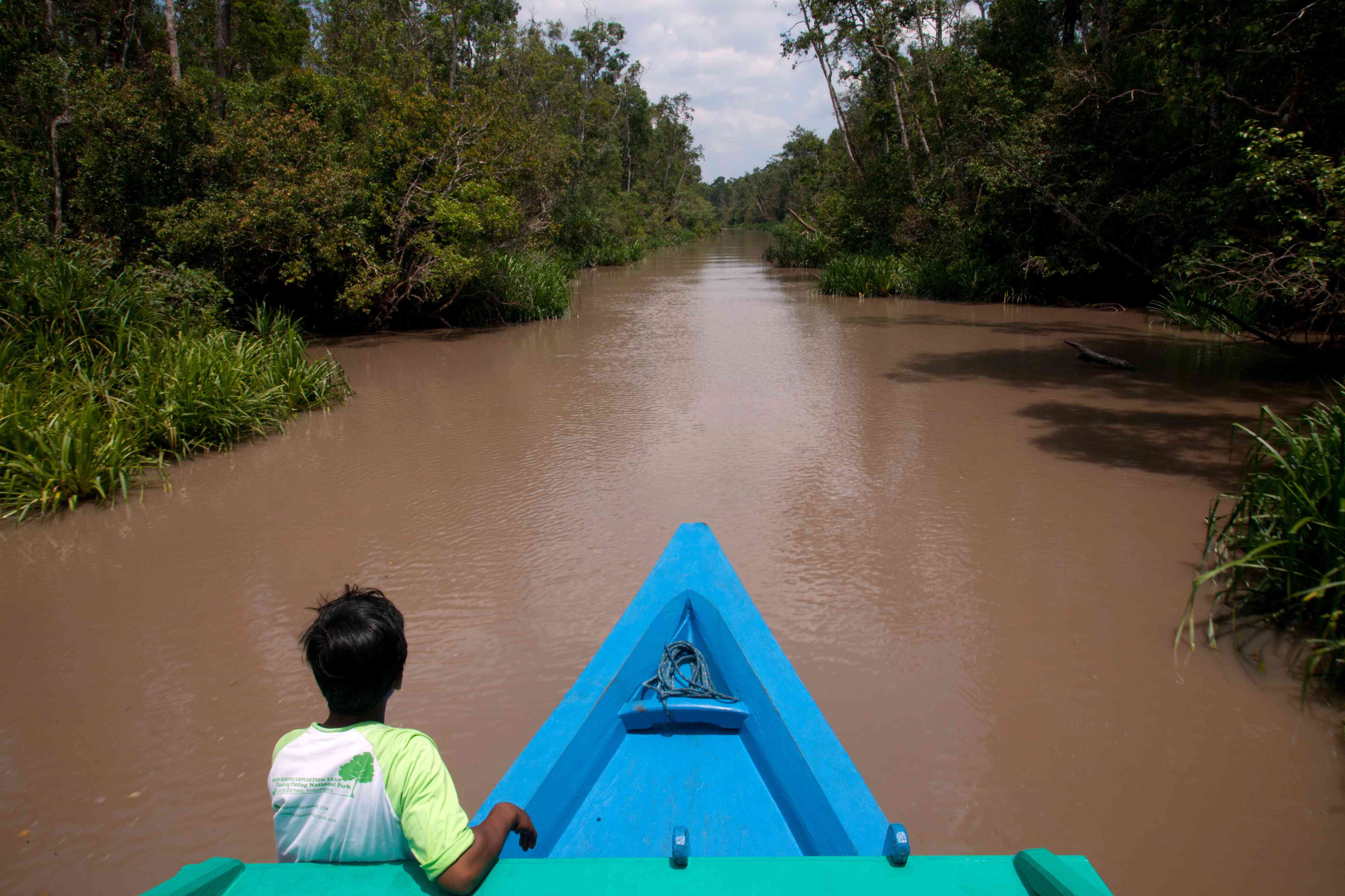 A boat and guide on a muddy river in Tanjung Puting, Kalimantan