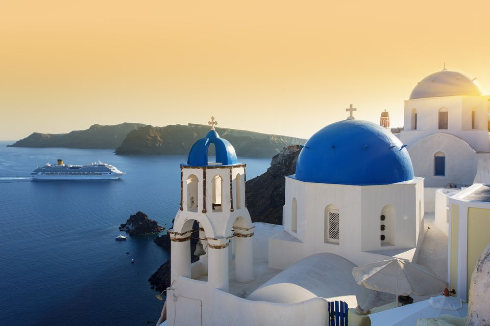 Blue domed churches at sunset, Oia, Santorini with a cruise ship in the background