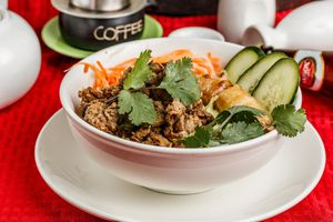 Bowl of bun thit nuong cha: vermicelli noodles with Grilled pork, pork egg roll, cucumber, and cilantro
