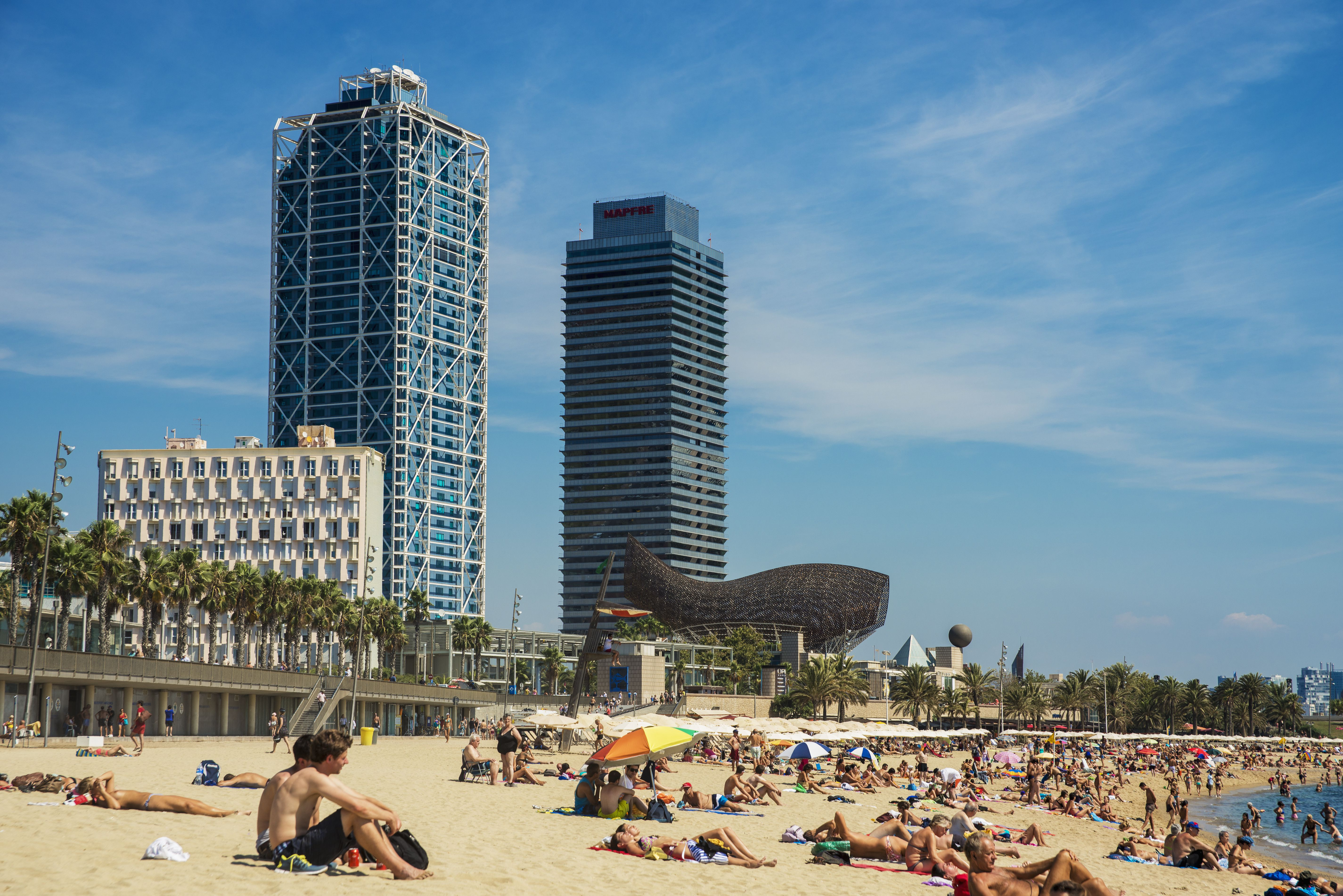 A Crowded Barceloneta Beach With Skysers In The Distance