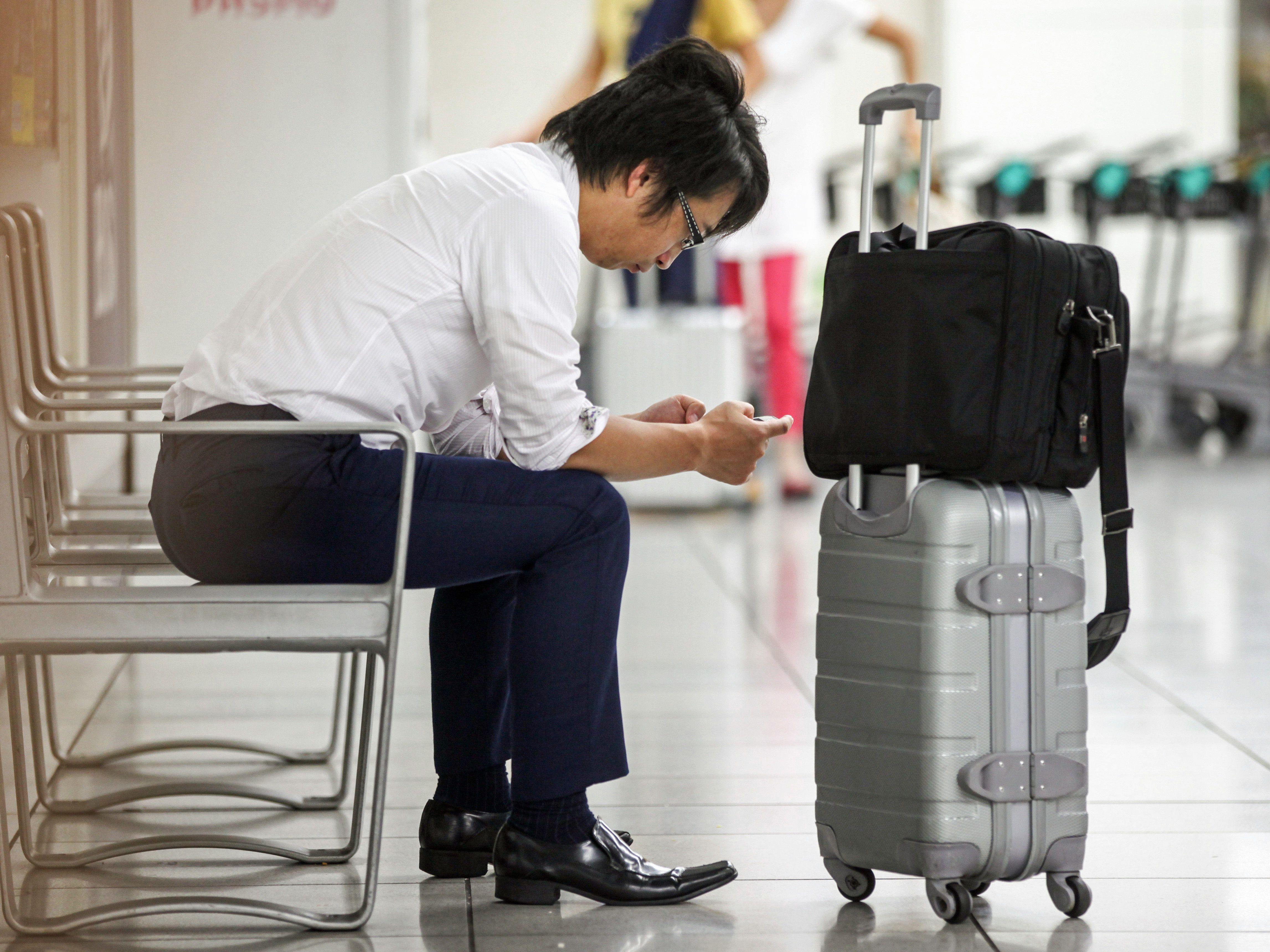 hombre en su teléfono inteligente en las terminales del aeropuerto
