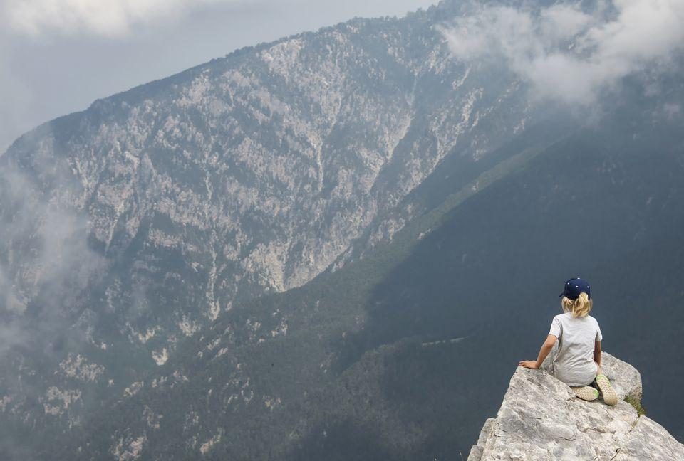 Chico excursionista mira desde la cresta de la alta cresta, el Monte Olimpo, hogar de los dioses de la antigua Grecia
