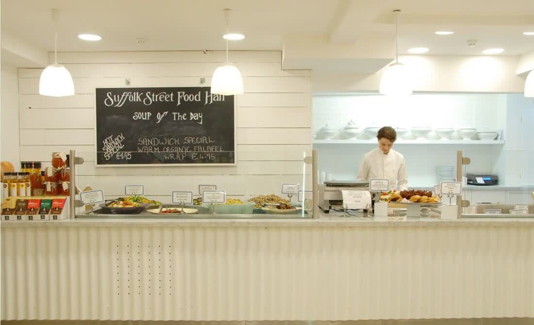 white jacketed server behind white counter