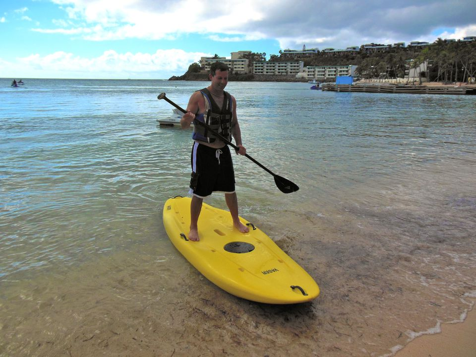 Deslizándose de regreso a la orilla mientras practica surf de remo en la Bahía de Bolongo