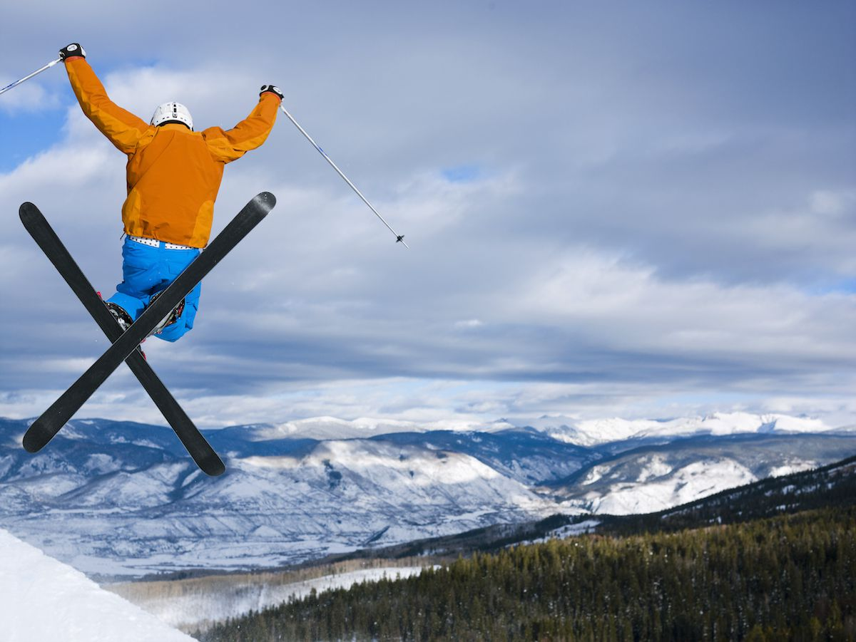 The Rocky Mountains of Colorado extends in the distance while a skier leaps in the air.