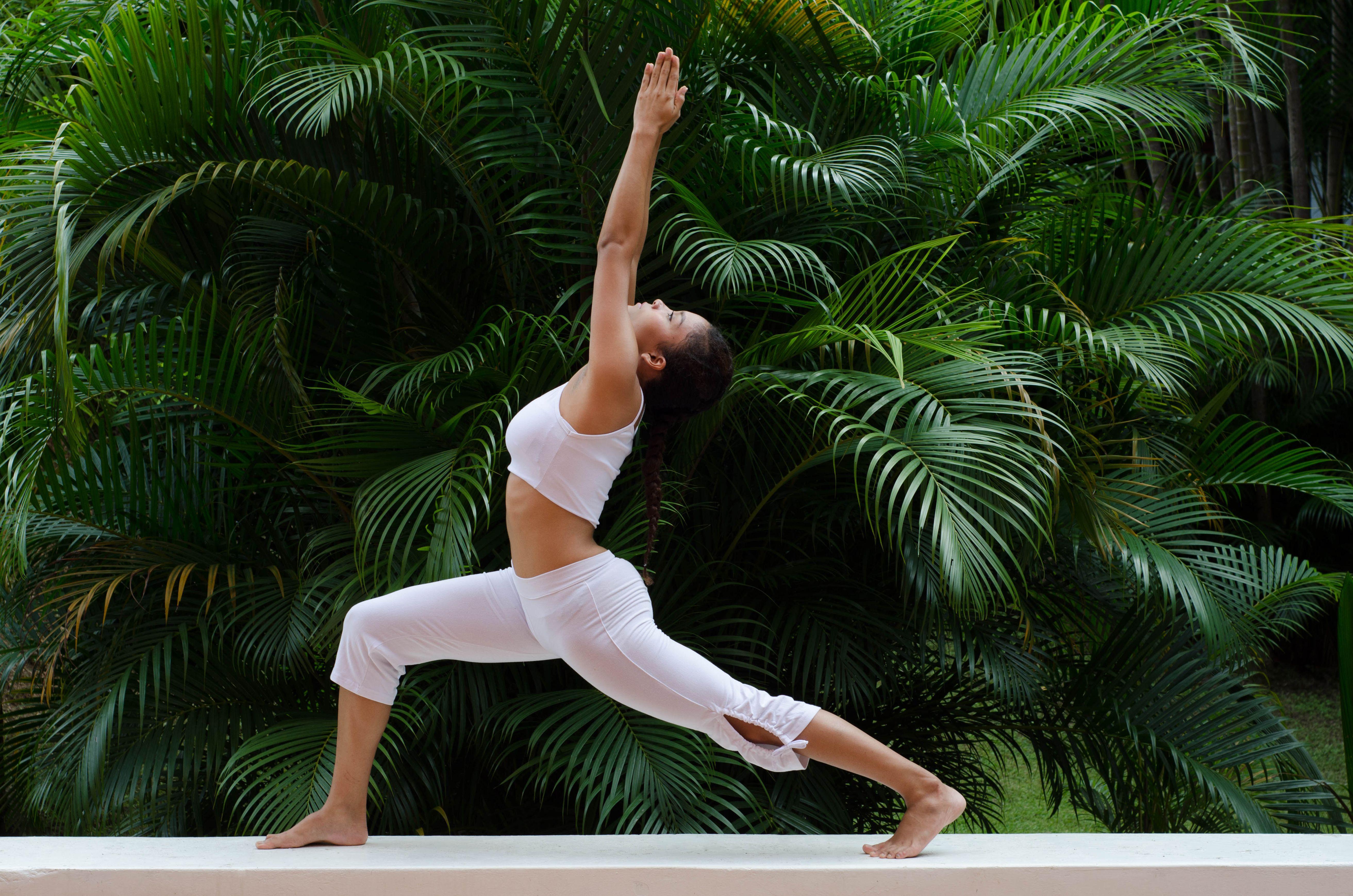 A woman doing a yoga pose on a garden