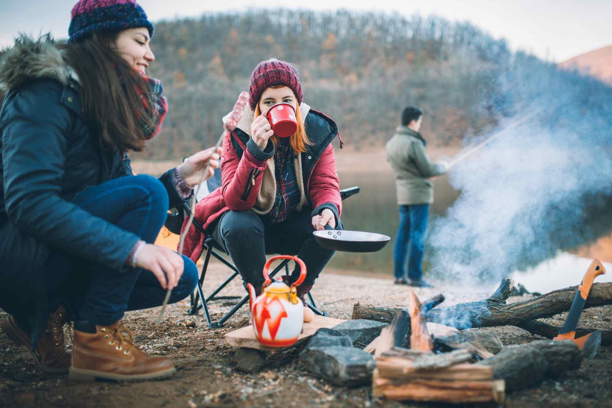 Mujeres jóvenes con ropa de abrigo mientras acampan