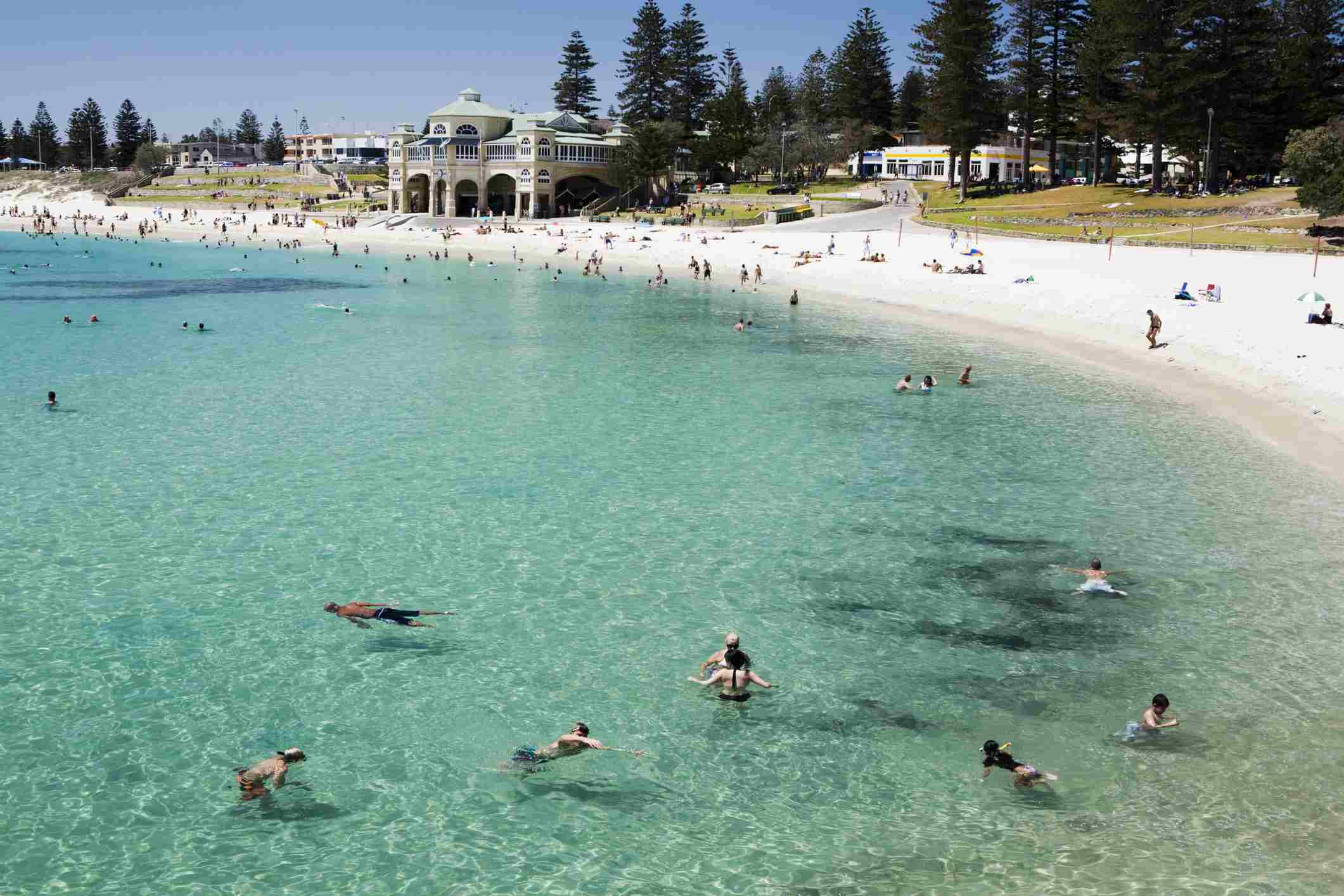 People swimming at Cottesloe Beach with Indiana Teahouse in the background.