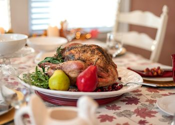A traditional roasted turkey on a table set for family Thanksgiving