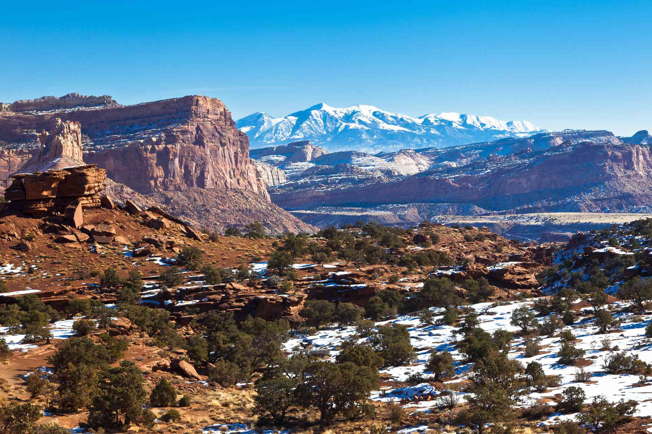 A view of the beautiful terrain in Capitol Reef National Park in Utah with snow capped mountains in the distance.