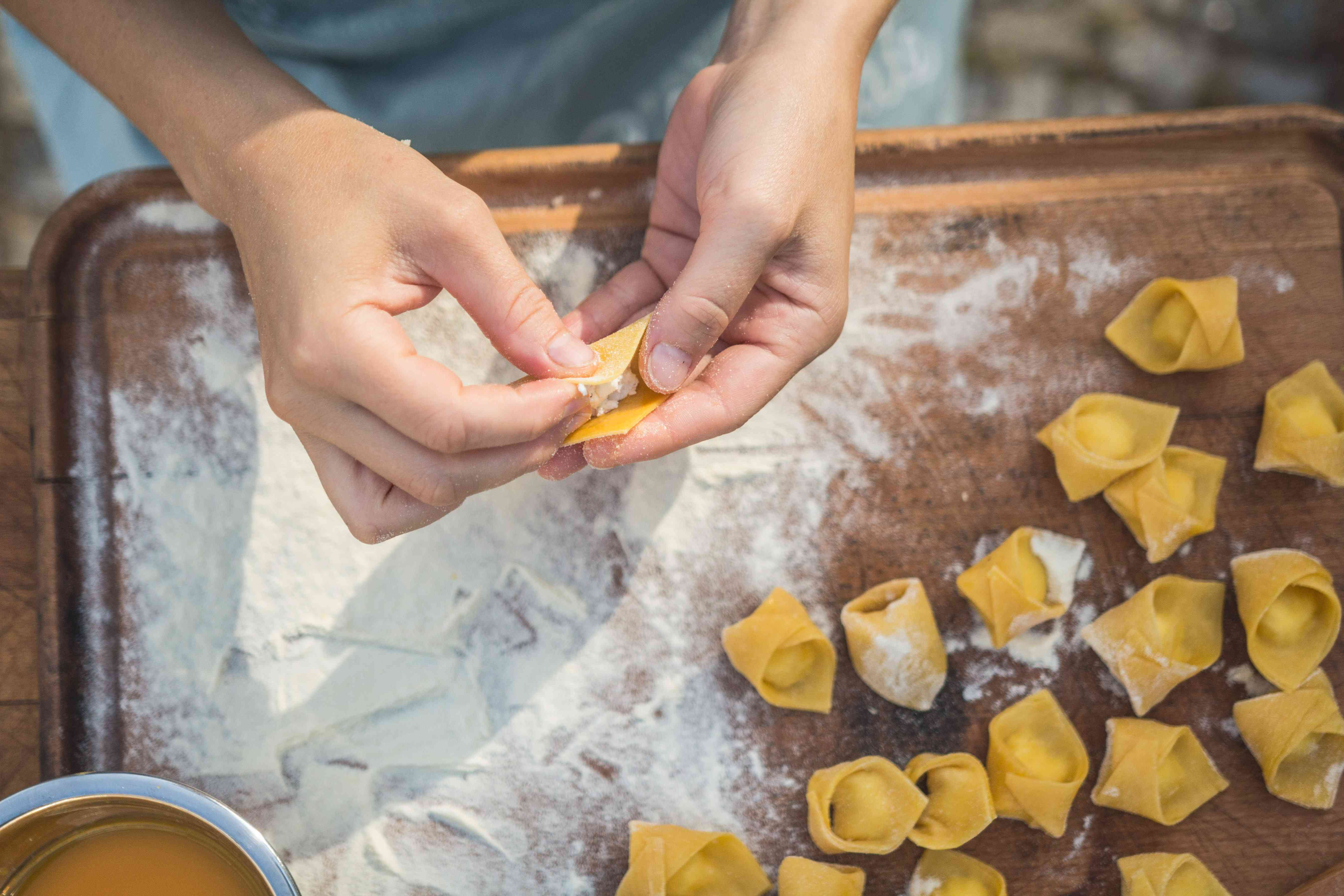 Young woman chef preparing handmade tortellini stuffed with ricotta and cheese.