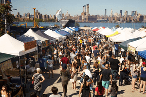 crowds of people shopping at food vendors tents in East River Park with Manhattan skyline in the background