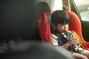 Toddler Boy Drinking In Carseat