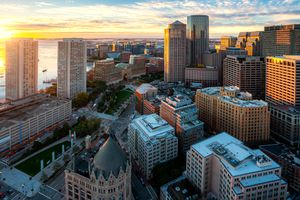 Aerial view of Boston Harbor and Financial District at sunset in Boston, Massachusetts, USA.