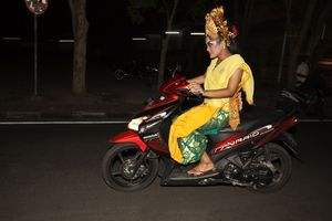 A costumed dancer riding a motorbike home at night in Ubud, Bali