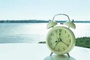 Close-Up Of Alarm Clock By Sea Against Sky