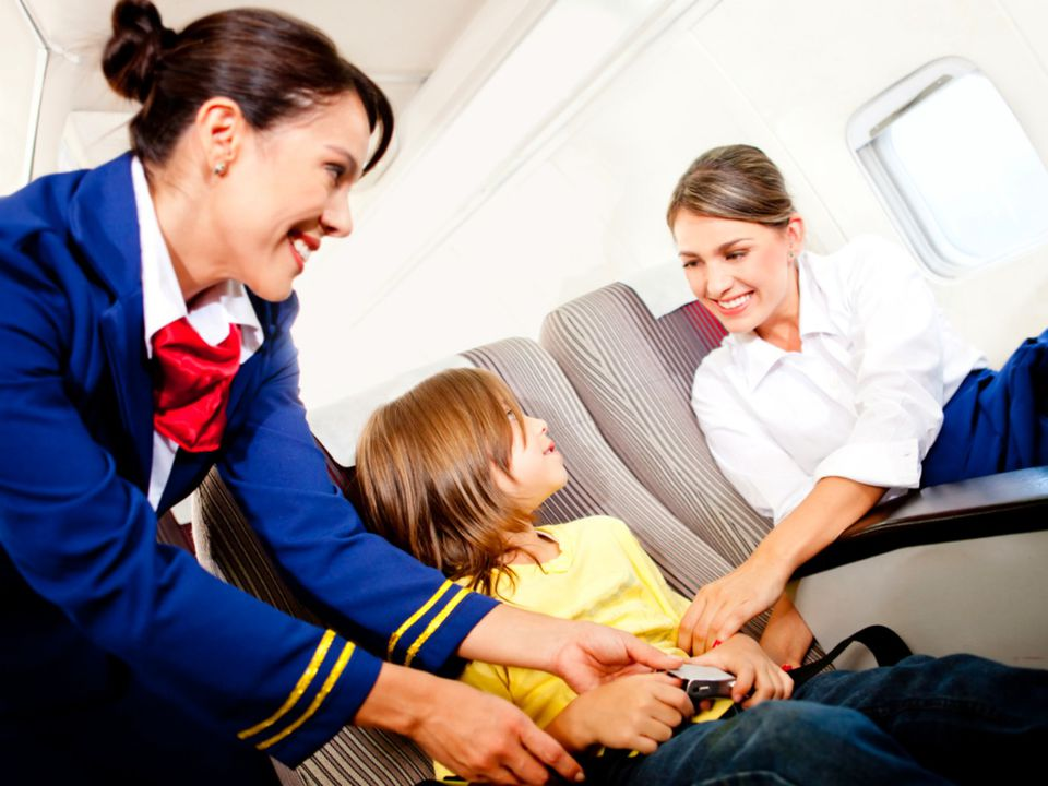 woman and stewardess helping buckle a child in