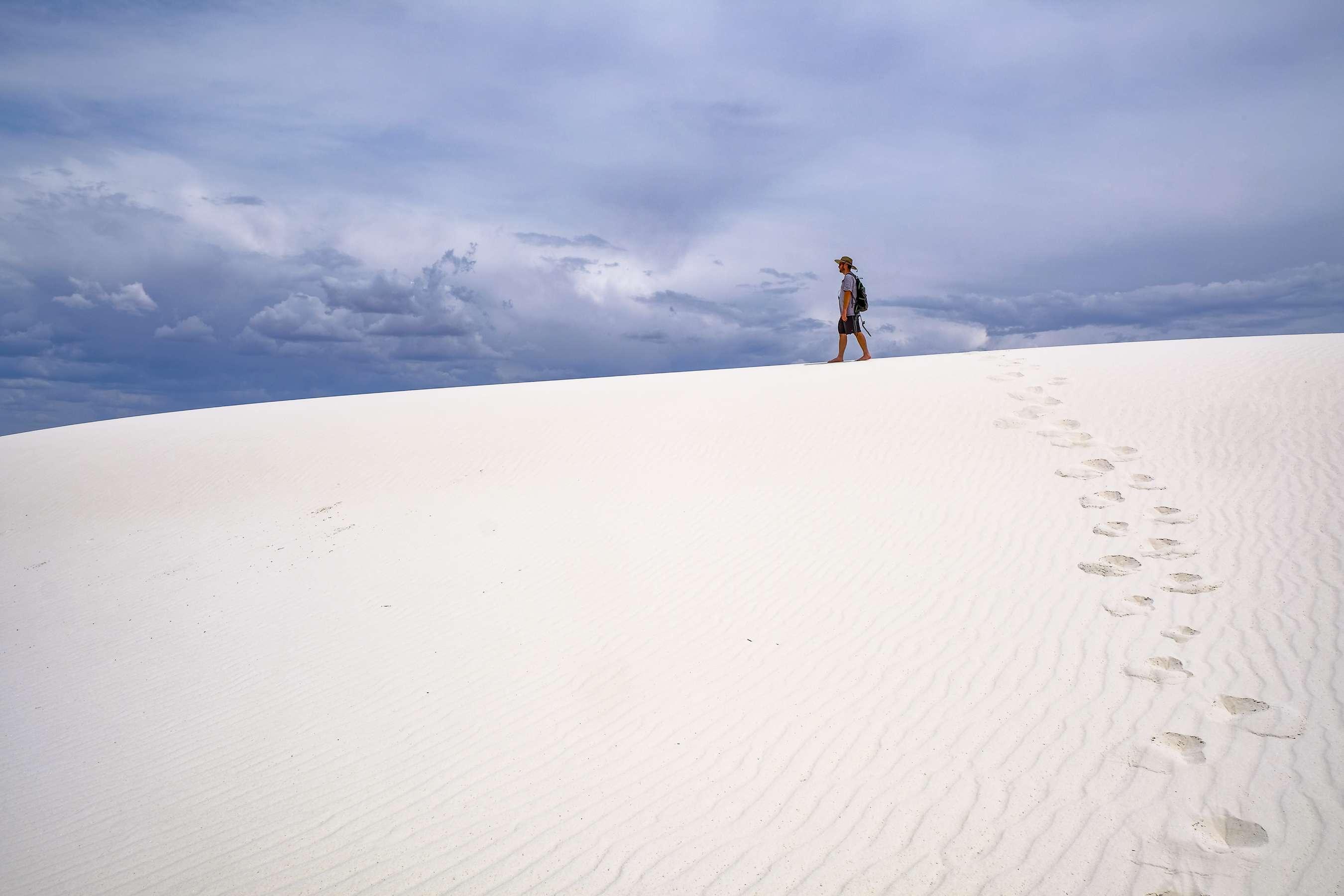 A man walking through white sands