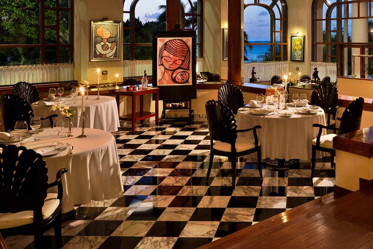 Le Basilic Restaurant Cancun dining room with art on the walls