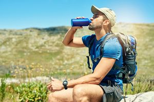 Cropped shot of a young man taking a break to drink water while out on a hike