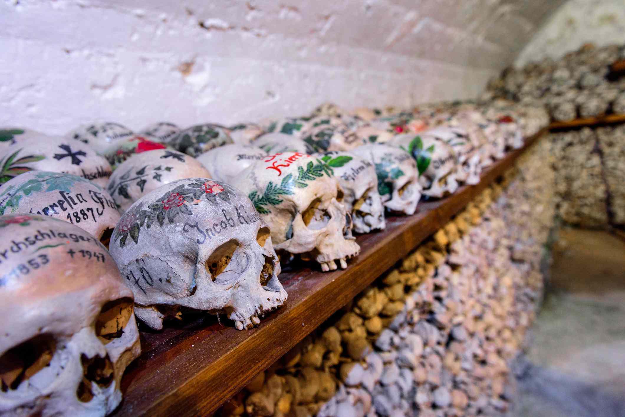 Colorful skulls in the Hallstatt Ossuary or Beinhaus (bone house)
