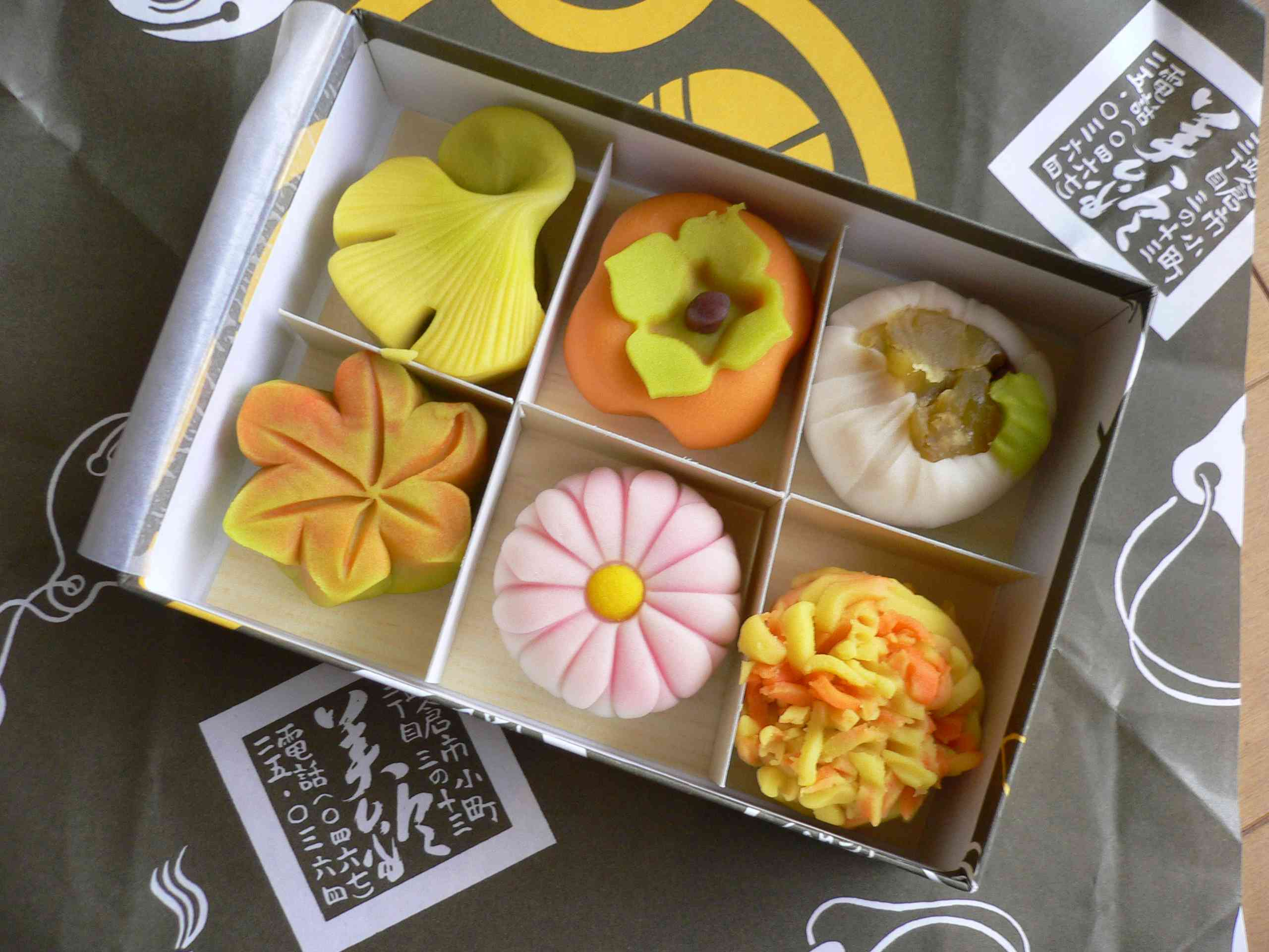 box of six decorative desserts in different shapes like a gingko leaf, flower, and persimmon