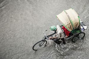 A man pushes a rickshaw during monsoon season in India