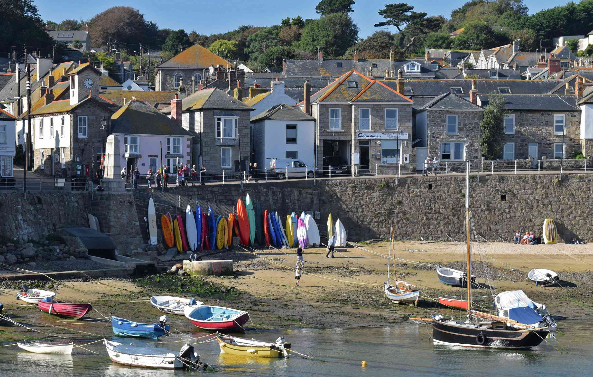 Mousehole Harbour with small boats and seawall backed by fishermen's cottages.