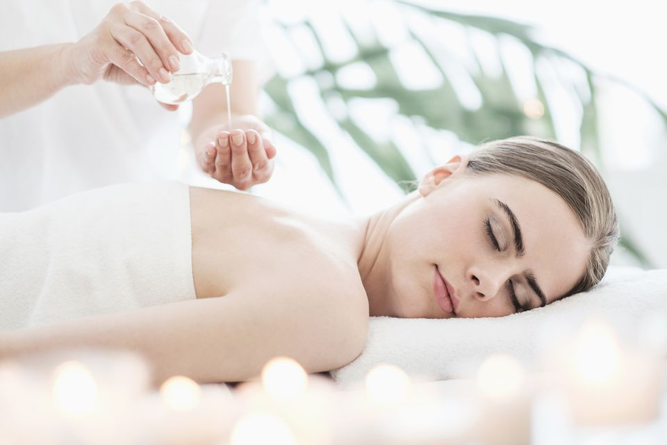 USA, New Jersey, Therapist putting massaging oil on young woman in spa