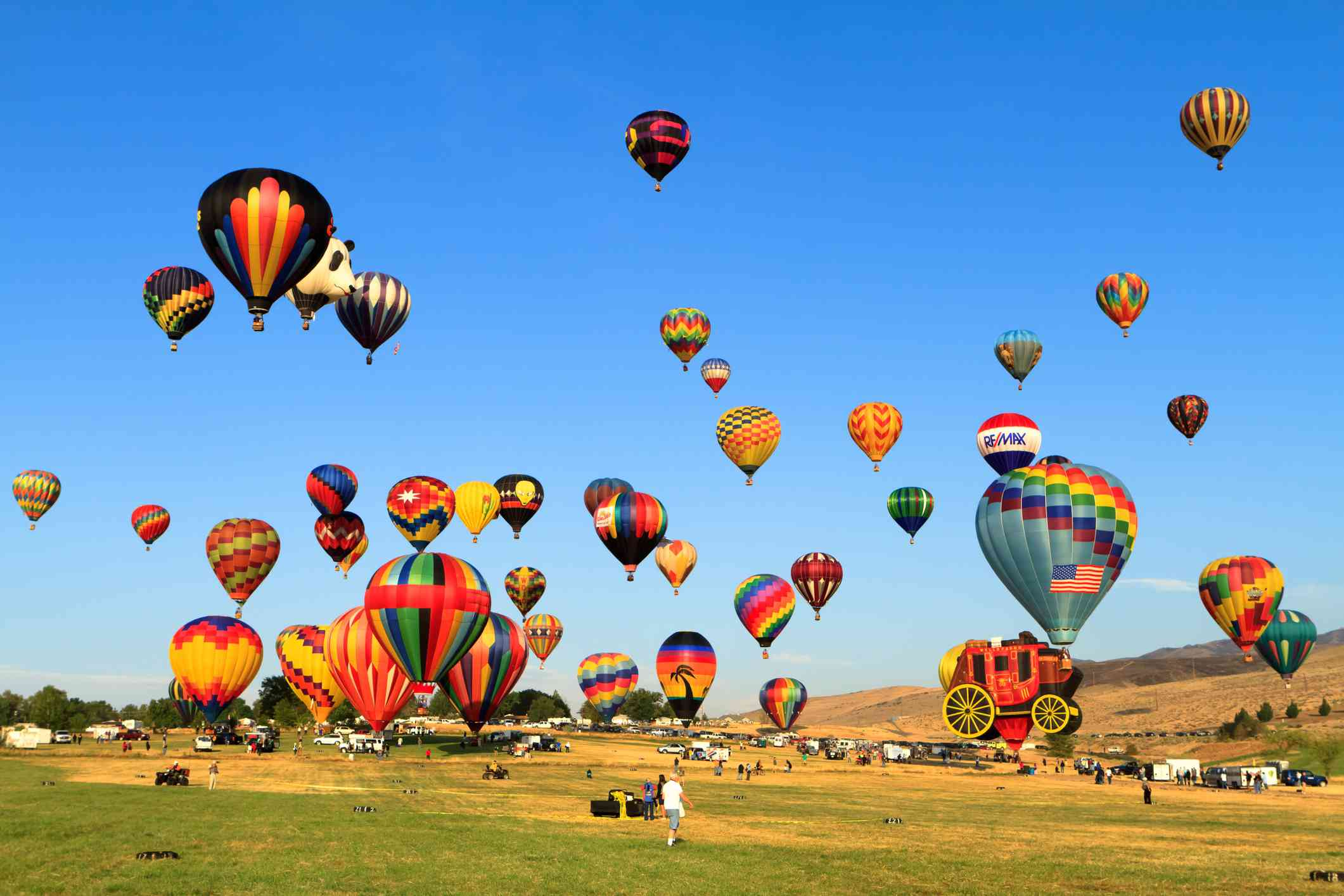 field near Reno, Nevada with dozens of colorful hot air balloons