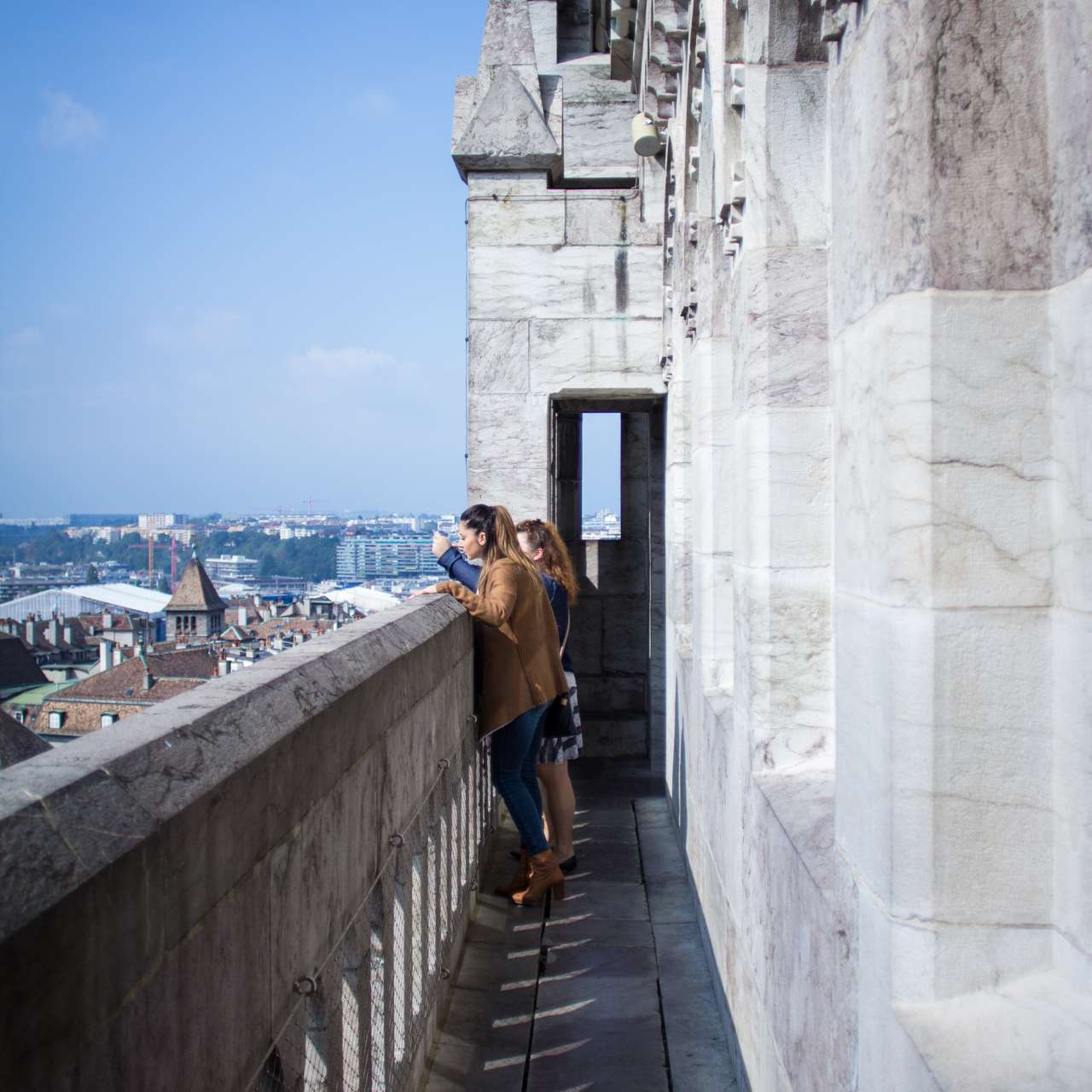 People standing on the roof of St. Pierre Cathedral, looking at the city below