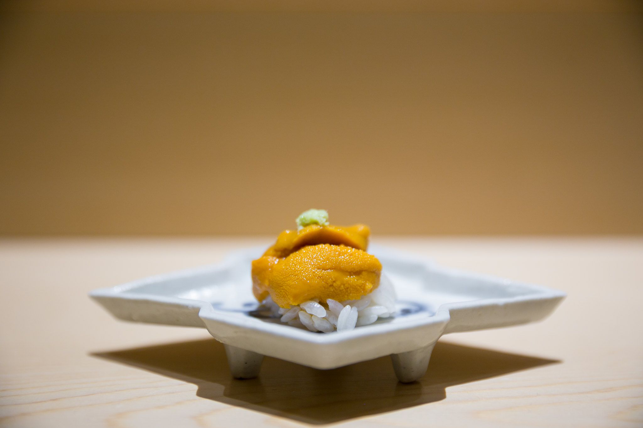 sea urchin over rice on a white plate