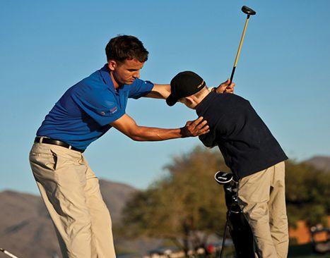 man teaching boy how to golf