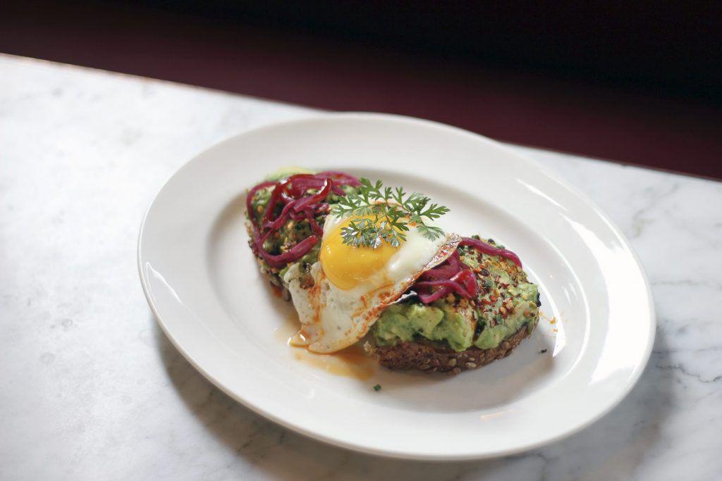 plato blanco con puré de aguacate sobre pan integral cubierto con cebolla roja en escabeche, un huevo soleado hacia arriba