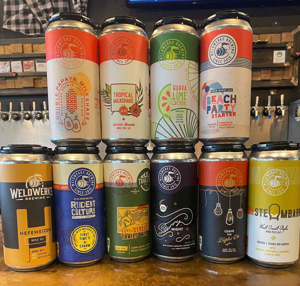 Several different cans of beer stacked on top of each other showing the variety sold