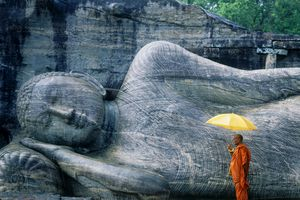 A monk in orange robes stands in front of a Buddha statue in Sri Lanka