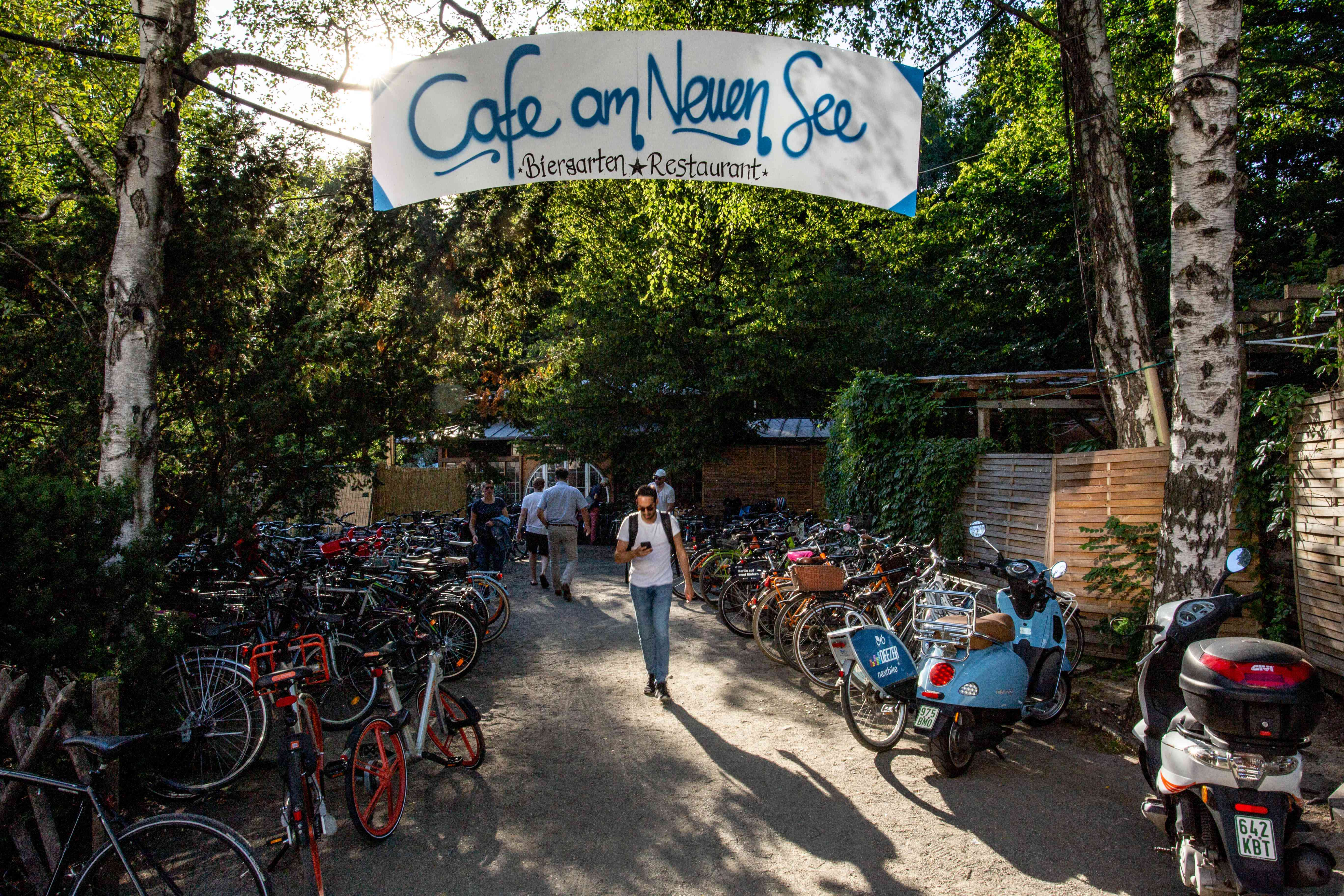 The entrance to Cafe am Neuen See and rows of bikes parked outside the sign