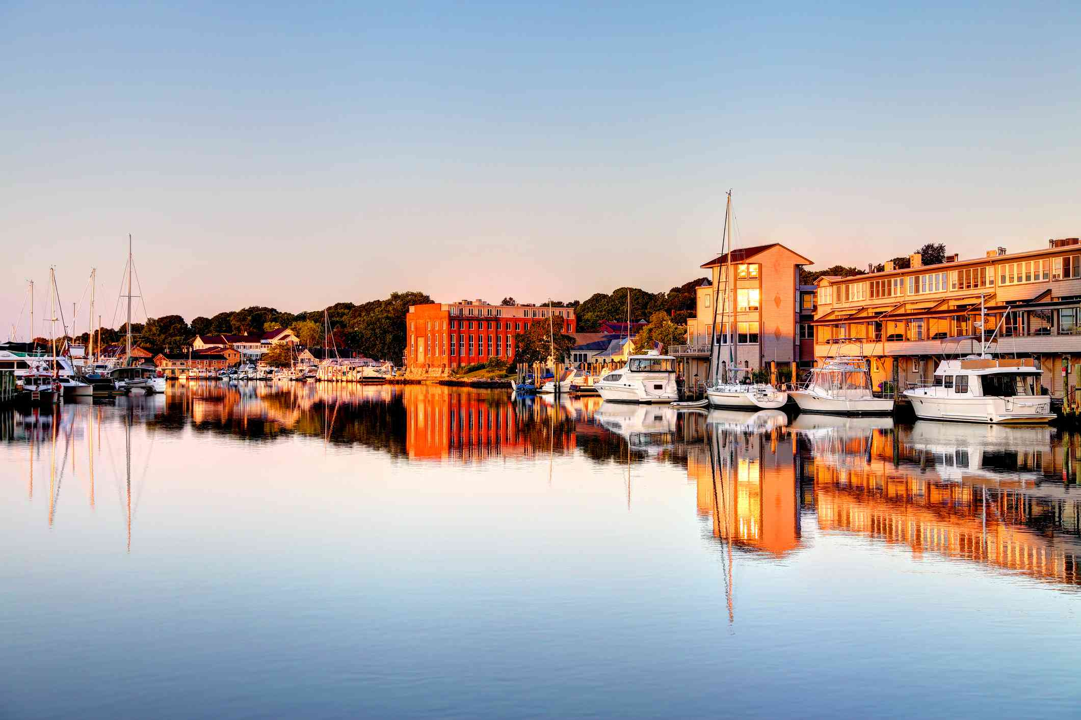 houses and boats reflected on still water in Mystic, Conn.