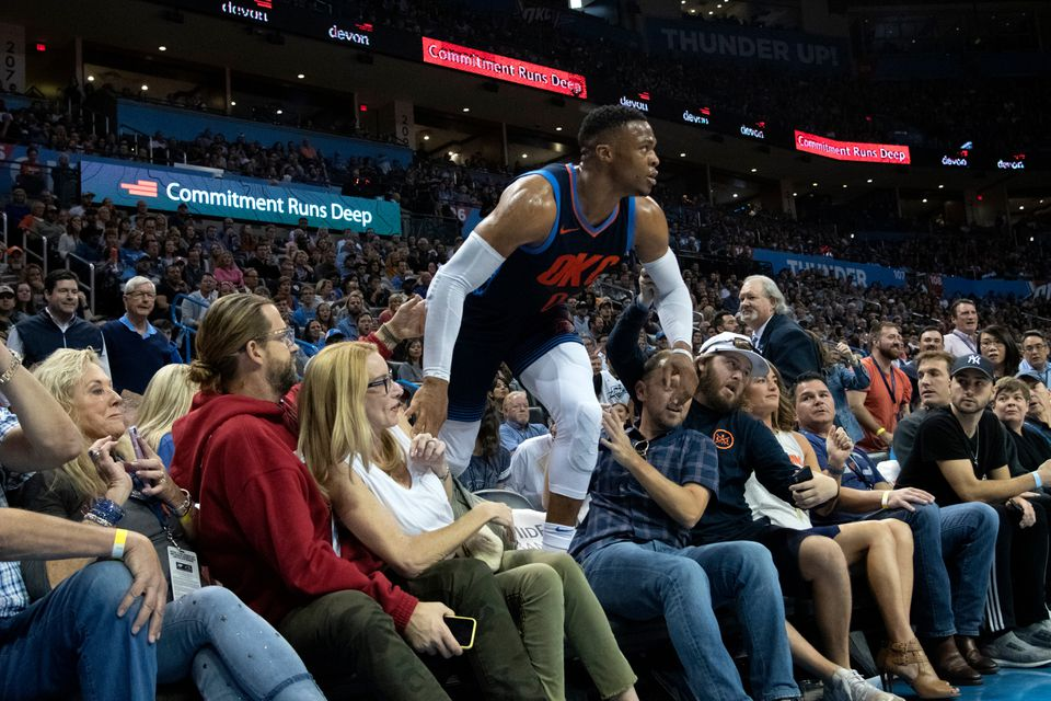 Russell Westbrook of the OKC Thunder climbs through a crowd of ticketholders in 2018 in Oklahoma City