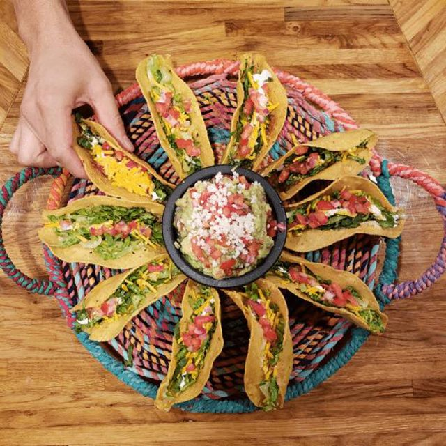 A circle dish of tacos with a hand reaching for one taco