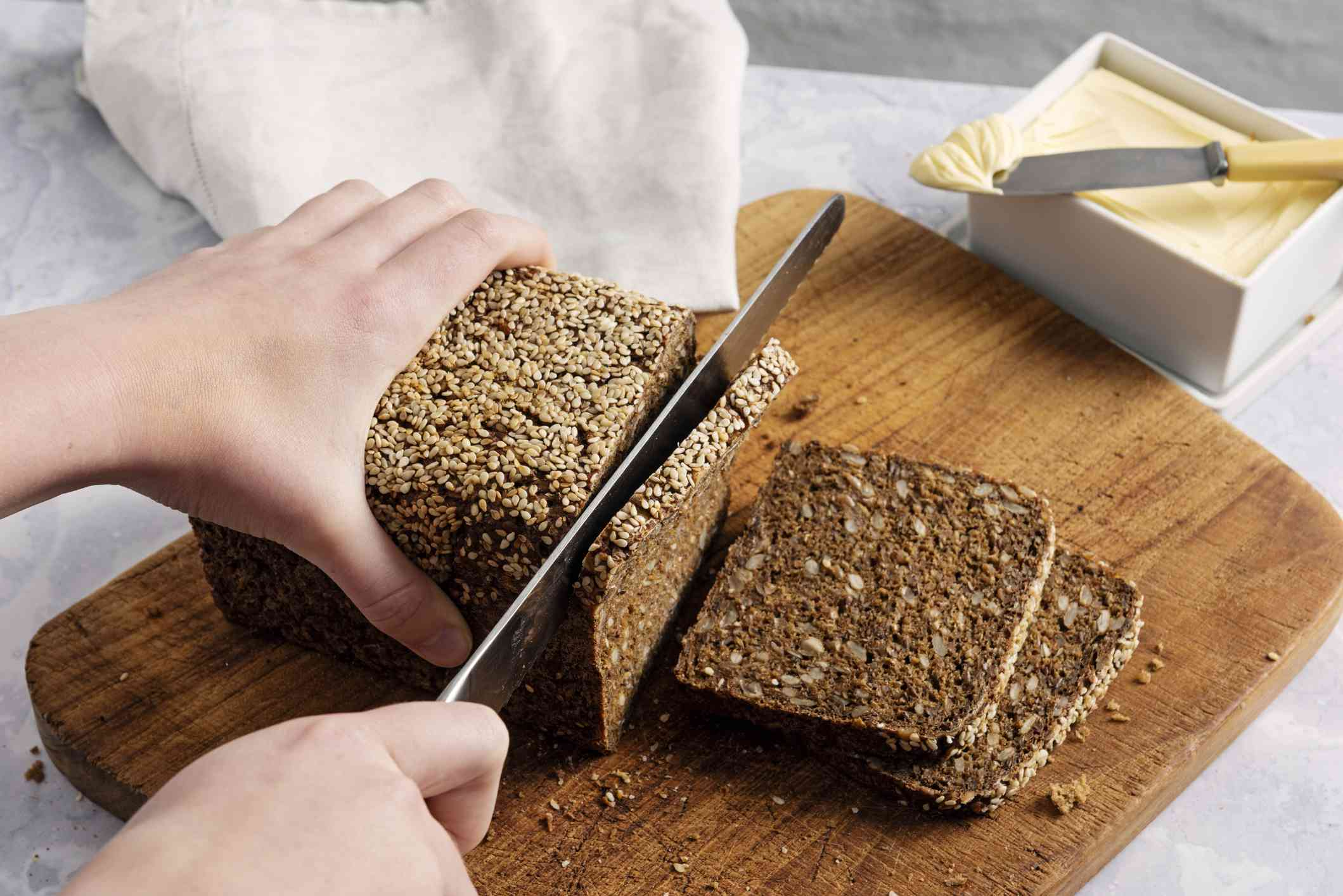 Person cutting a loaf of rye bread into slices