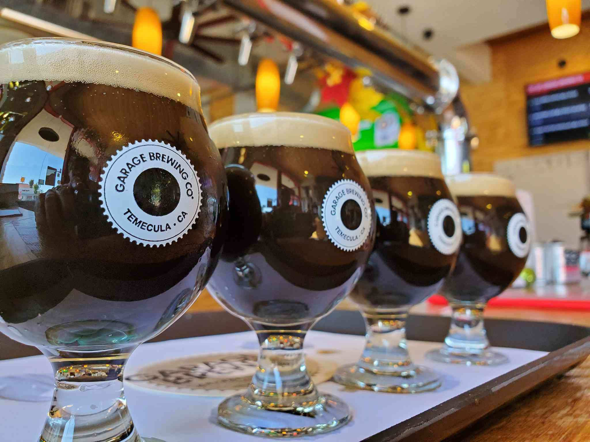 Four dark stout beers on a tray