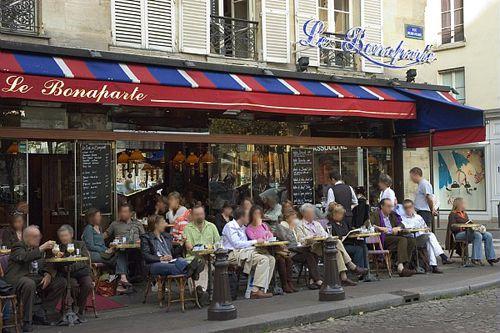 Bebiendo café y mordisqueando sabrosa comida a la sombra de la Basílica del Sacré-Coeur