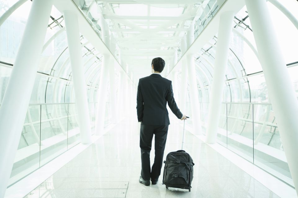 Male traveler at the airport with a rolling carry-on bag