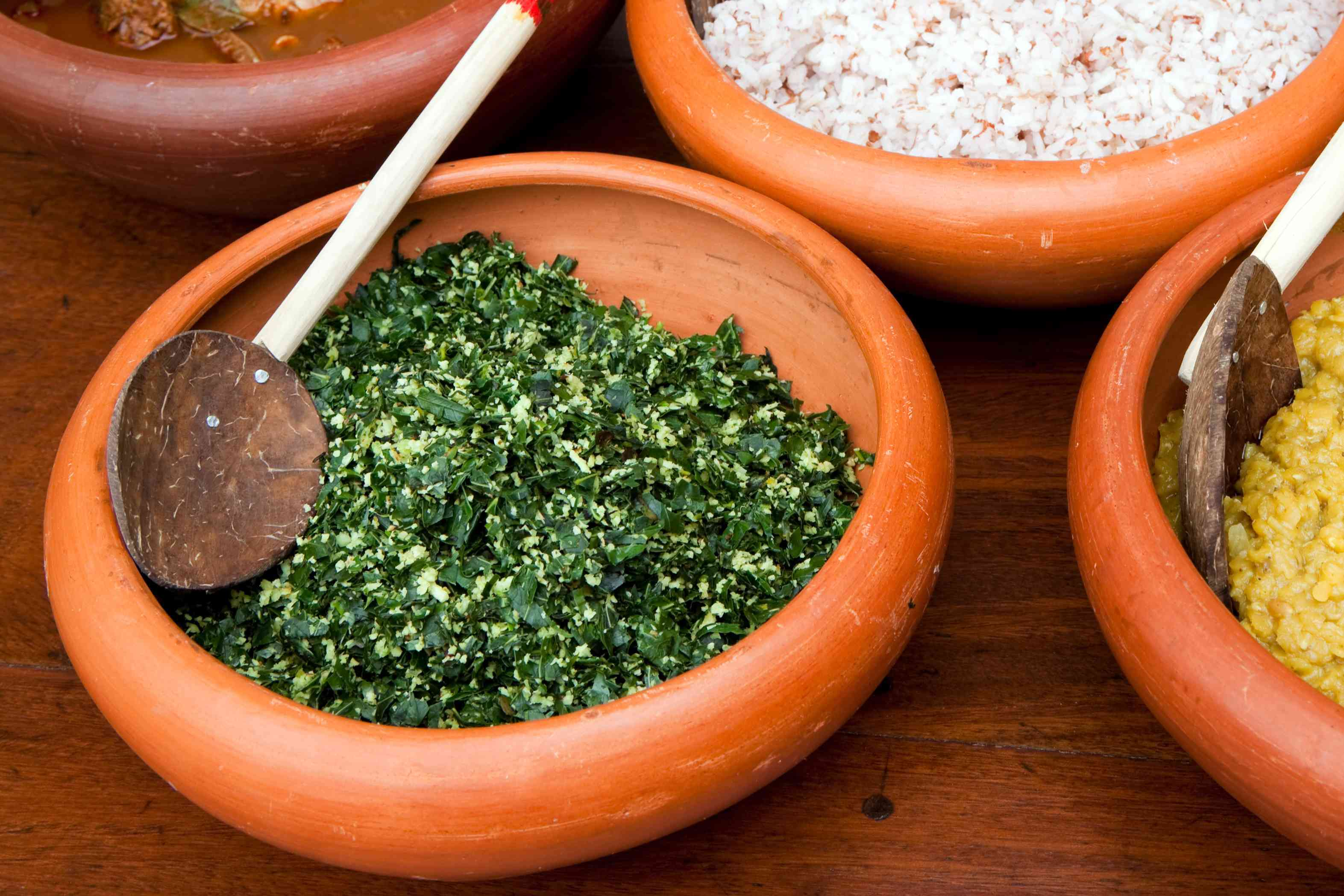 Sri Lankan mallung, shredded greens with a wooden spoon in an orange bowl