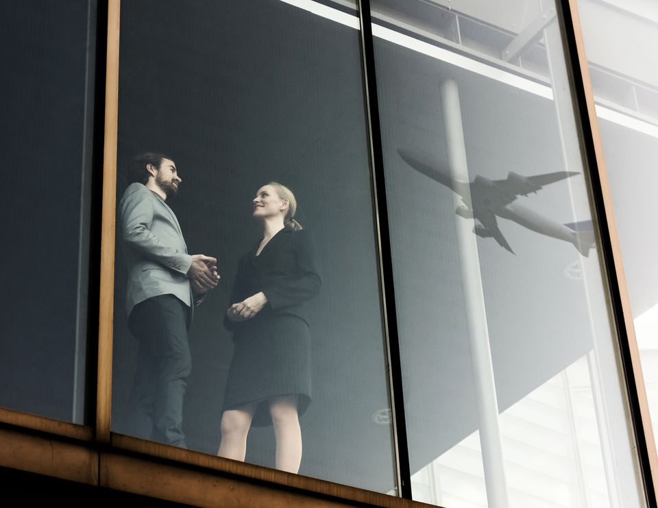 business travelers talking with airplane in window reflection