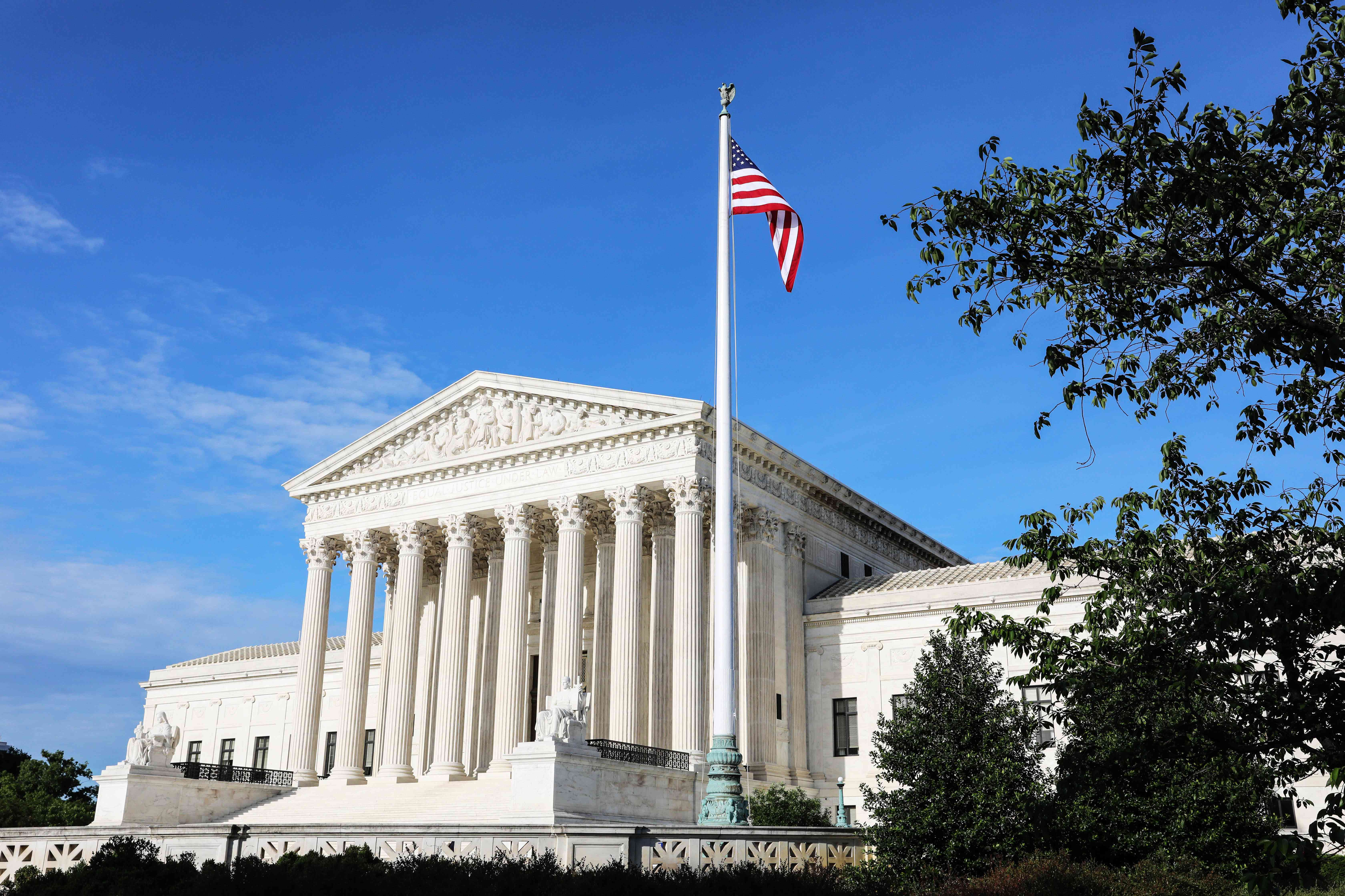 Exterior of the Supreme Court with the american flag waving